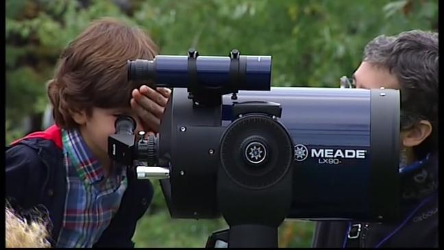 Un niño mira por un telescopio