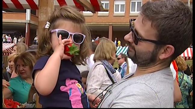 Una niña disfruta de una fresa en el festival de Candamo