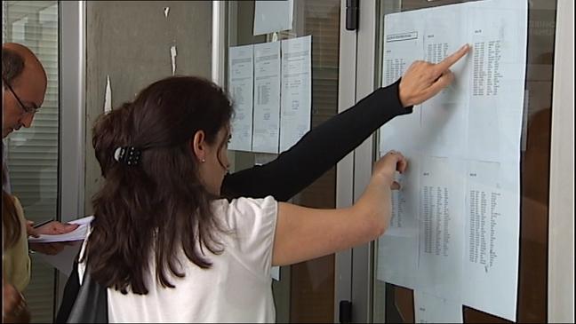 Opositores a maestros miran las listas para examinarse