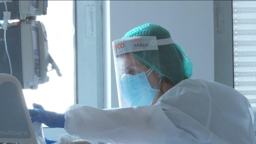 Sanitaria revisando unos datos de una máquina de hospital